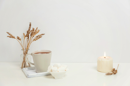 Natural eco home decor with cup coffee marshmallow candle on wooden tray. Early morning breakfast lifestyle background. Interior decoration with hot drink mug. Hygge scandinavian style copy space