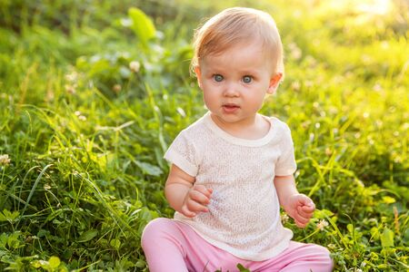 Sweet happy little baby girl sitting on grass in park, garden, meadow. Laughing, happiness, enjoying fresh air in forrest in sunny summer day. Portrait of happy cute babe toddler outdoor Stock Photo - 133851648