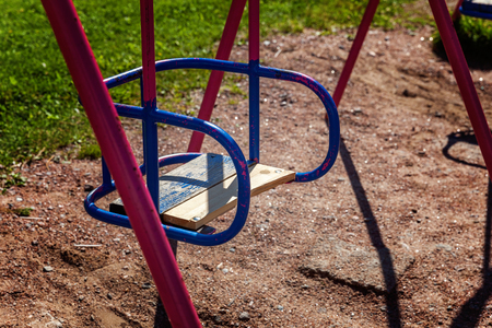 Close up of old metal blue and purple baby swing on kids playground
