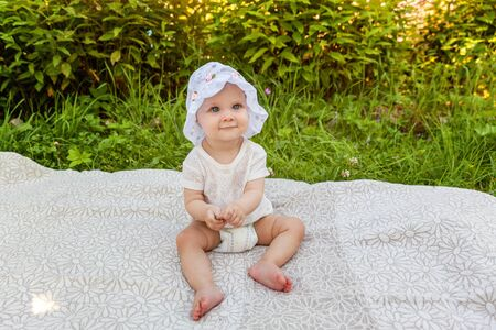 Sweet happy little baby girl sitting on grass in park, garden, meadow. Laughing, happiness, enjoying fresh air in forrest in sunny summer day. Portrait of happy cute babe toddler outdoor
