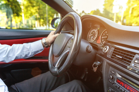 Male hands on steering wheel closeup. Sunny day Stock Photo