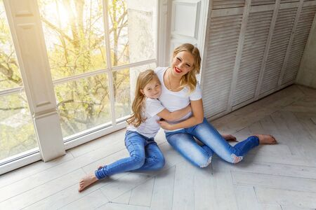 Mother hugging child. Woman and girl relax and playing in bedroom near windiow. Happy family at home. Mom playing with her daughter. Family, maternity, tenderness, parenthood, responsibility concept Reklamní fotografie - 133851961