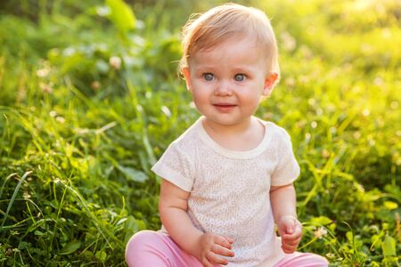 Sweet happy little baby girl sitting on grass in park, garden, meadow. Laughing, happiness, enjoying fresh air in forrest in sunny summer day. Portrait of happy cute babe toddler outdoor Stock Photo - 133851962