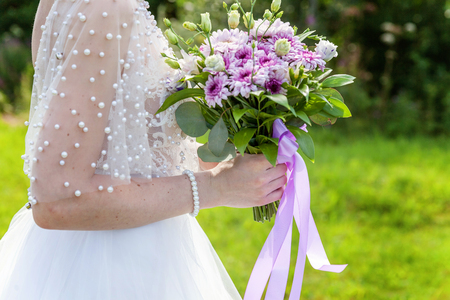 Details of the wedding dress and brides hands ring with bouquet