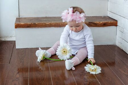 Little smiling baby girl one year old wearing spring wreath siting on floor in bright light living room near window and playing with gerbera flowers. Happy kid playing at home. Childhood concept