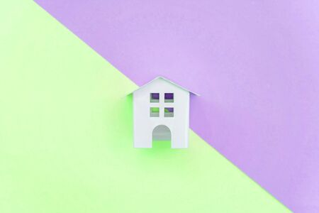 Miniature white toy house on violet and green pastel color paper geometric flat lay background. Mortgage property insurance dream home concept. Copy space for advertisement