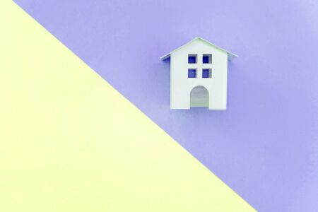 Miniature white toy house on violet and yellow pastel color paper geometric flat lay background. Mortgage property insurance dream home concept. Copy space for advertisement