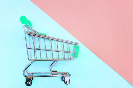 Small supermarket grocery push cart for shopping toy with wheels on pink and blue pastel color paper geometric flat lay background. Concept of shopping. Copy space for advertisement Stock fotó