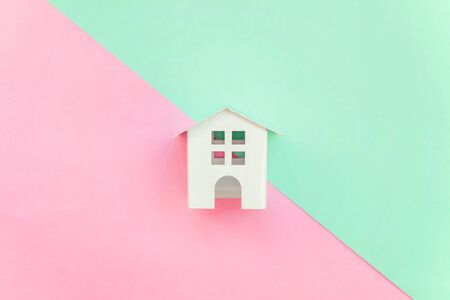 Miniature white toy house on pink and green pastel color paper geometric flat lay background. Mortgage property insurance dream home concept. Copy space for advertisement