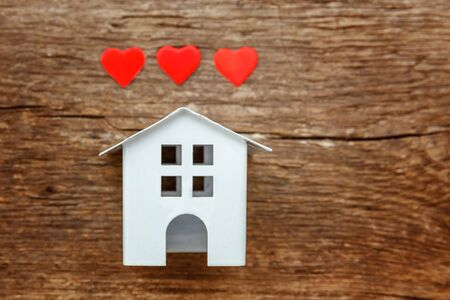 Miniature white toy house with red hearts on a rustic old vintage wooden background. Mortgage property insurance dream home concept Stock fotó - 125684111