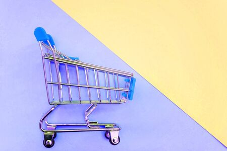 Small supermarket grocery push cart for shopping toy with wheels on yellow and blue pastel color paper geometric flat lay background. Concept of shopping. Copy space for advertisement Stock fotó