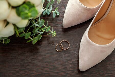 Beautiful wedding bouquet of flowers rings bridal shoes on wooden background. Declaration of love, spring. Wedding card, Valentines Day greeting. Wedding rings. Wedding day details