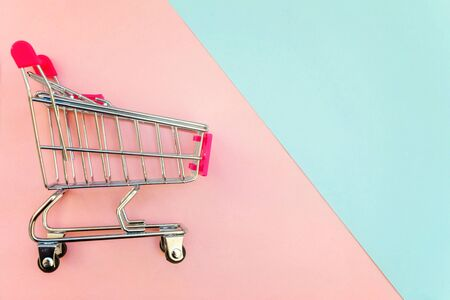 Small supermarket grocery push cart for shopping toy with wheels and pink plastic elements on pink and blue pastel color paper geometric flat lay background. Concept of shopping. Copy space for advertisement