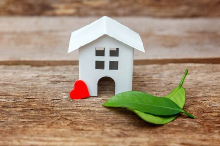 Miniature white toy model house with green leaves and red hearts on wooden backgdrop. Eco Village, abstract environmental background. Real estate mortgage property insurance dream home ecology concept