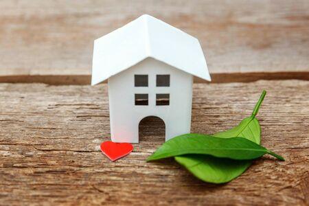 Casa modello giocattolo bianco in miniatura con foglie verdi e cuori rossi su sfondo in legno. Eco Village, sfondo ambientale astratto. Concetto di ecologia della casa dei sogni dell'assicurazione della proprietà ipotecaria immobiliare