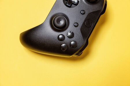 Black joystick gamepad, game console on yellow colourful trendy modern fashion pin-up background. Computer gaming competition videogame control confrontation concept. Cyberspace symbol