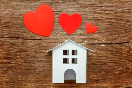 Miniature white toy house with red hearts on a rustic old vintage wooden background. Mortgage property insurance dream home concept