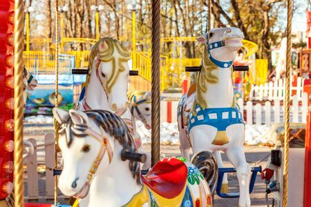 Children outdoor colourful vintage Merry-Go-Round flying horse carousel in amusement holliday park in city. Attraction detail horses and animals with lots gold paintwork on traditional retro carnival 免版税图像 - 125681747