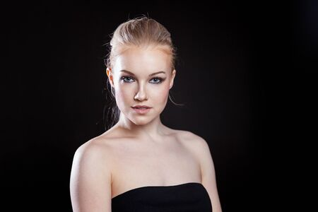 Beauty fashion model girl with long healthy smooth straight hair ponytail hairstyle on black background. Smiling pretty woman looking camera. Perfect Fresh Skin Portrait. Youth and Skin Care Concept Zdjęcie Seryjne