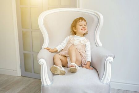 Sweet little girl in pastel pink dress at home sitting on modern cozy grey chair relaxing in white living room. Childhood, preschool, youth, relax concept