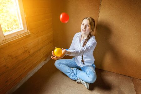 Young hipster woman sitting on floor and juggling colored balls at home. Teen girl juggler learning agility control balance in her room Standard-Bild - 133852237
