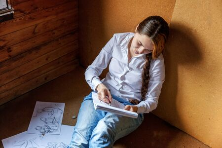 Young hipster woman sitting on floor and drawing sketch in album at home. Teen girl learning sketching picture in her room. Hobby, lifestyle, relax, art, leisure, education concept Standard-Bild - 133852242