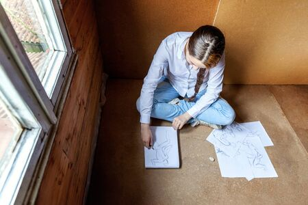 Young hipster woman sitting on floor and drawing sketch in album at home. Teen girl learning sketching picture in her room. Hobby, lifestyle, relax, art, leisure, education concept Standard-Bild - 133852248