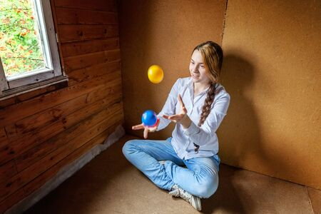 Young hipster woman sitting on floor and juggling colored balls at home. Teen girl juggler learning agility control balance in her room Standard-Bild - 133852254