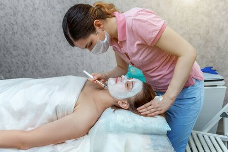 Close-up of young beauty brunette woman getting face treatment with white nourishing creme in spa salon. Face massage. Spa skin and body care. Skincare cleansing cosmetic spa relax concept 免版税图像