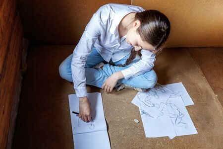 Young hipster woman sitting on floor and drawing sketch in album at home. Teen girl learning sketching picture in her room. Hobby, lifestyle, relax, art, leisure, education concept Standard-Bild - 133852258