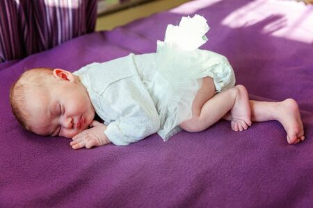Soft portrait of peaceful sweet newborn infant baby lying on bed while sleeping in purple blanket background. Sweet dream, good night. Maternity family childhood innocence care concept Stock Photo