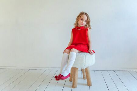 Sweet happy little girl in red dress sitting on chair against white wall background in bright room