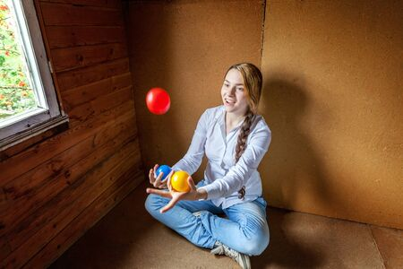 Young hipster woman sitting on floor and juggling colored balls at home. Teen girl juggler learning agility control balance in her room Standard-Bild - 133852590