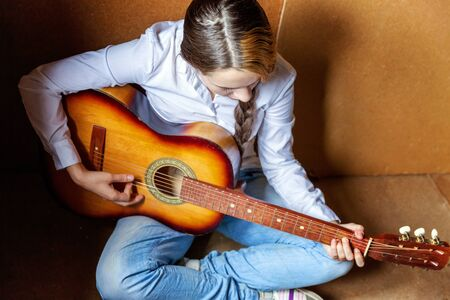 Young hipster woman sitting on floor and playing guitar at home. Teen girl learning to play song and writing music in her room. Hobby, lifestyle, relax, Instrument, leisure, education concept