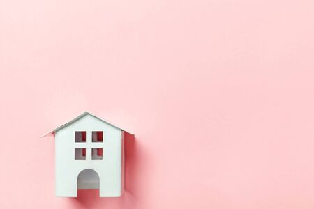 Simply design with miniature white toy house isolated on pink pastel colorful trendy background. Mortgage property insurance dream home concept. Flat lay top view copy space