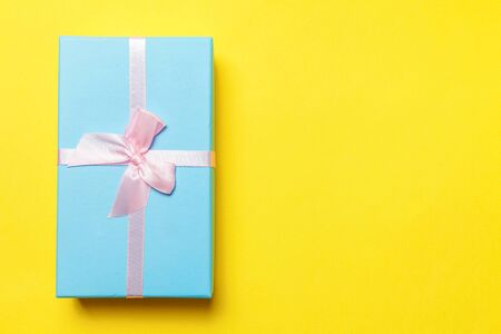 Christmas New Year birthday valentine celebration present romantic concept. Gift box wrapped blue paper isolated on yellow colourful trendy modern fashion background. Flat lay top view copy space