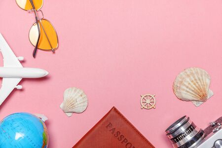 Vacation travel summer weekend adventure trip concept. Minimal simple flat lay with plane vintage camera passport sunglasses globe and shell on pink pastel trendy modern background. Tourist essentials
