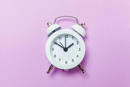 Ringing twin bell vintage classic alarm clock Isolated on purple violet pastel colourful background. Rest hours time of life good morning night wake up awake concept. Flat lay top view copy space