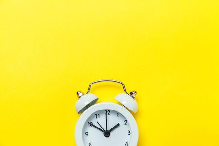 Ringing twin bell vintage classic alarm clock Isolated on yellow colourful trendy modern background. Rest hours time of life good morning night wake up awake concept. Flat lay top view copy space Stock Photo