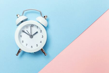 Ringing twin bell vintage classic alarm clock Isolated on blue pink pastel colorful trendy background. Rest hours time of life good morning night wake up awake concept. Flat lay top view copy space
