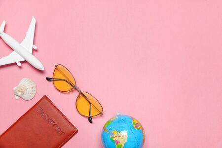Vacation travel summer weekend sea adventure trip concept. Minimal simple flat lay with plane passport sunglasses globe and shell on pink pastel trendy modern background. Tourist essentials 版權商用圖片