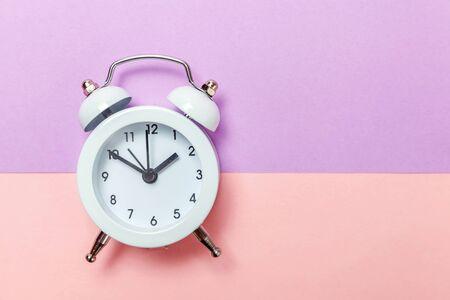 Dzwoni podwójny dzwon vintage klasyczny budzik izolowany na fioletowym różowym pastelowym kolorowym tle. Godziny odpoczynku czas życia dzień dobry w nocy obudź się na jawie. Płaska przestrzeń do kopiowania z widokiem z góry