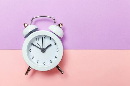 Ringing twin bell vintage classic alarm clock Isolated on purple pink pastel colourful background. Rest hours time of life good morning night wake up awake concept. Flat lay top view copy space