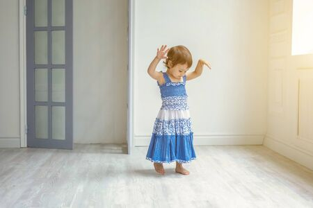 Little cute sweet smiling girl in blue dress dancing in bright light living room at home.