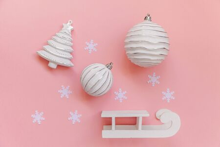 Simply minimal composition winter objects ornament ball fir tree sled isolated on pink pastel trendy background. Christmas New Year december time for celebration concept. Flat lay top view copy space Stock Photo