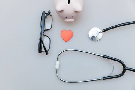 Medicine doctor equipment stethoscope or phonendoscope piggy bank glasses isolated on white background. Health care financial checkup or saving for medical insurance costs concept