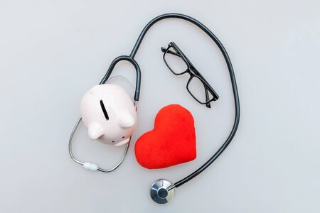 Medicine doctor equipment stethoscope or phonendoscope piggy bank glasses and red heart isolated on white background. Health care financial checkup or saving for medical insurance costs concept