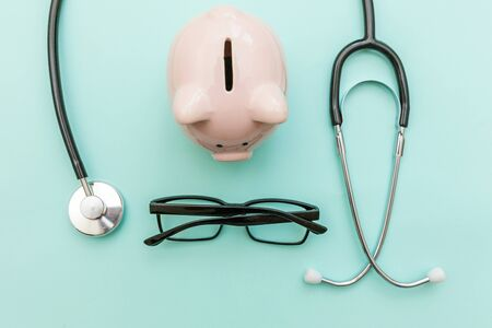Medicine doctor equipment stethoscope or phonendoscope piggy bank glasses isolated on trendy pastel blue background. Health care financial checkup or saving for medical insurance costs concept