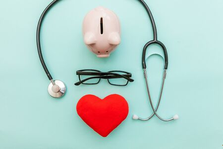 Medicine doctor equipment stethoscope or phonendoscope piggy bank glasses red heart isolated on trendy pastel blue background. Health care financial checkup or saving medical insurance costs concept