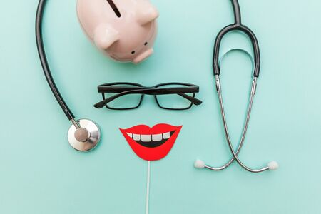 Health dental care concept. Medicine equipment stethoscope or phonendoscope glasses piggy bank sign of smile teeth isolated on trendy pastel blue background. Instrument device for dentist doctor